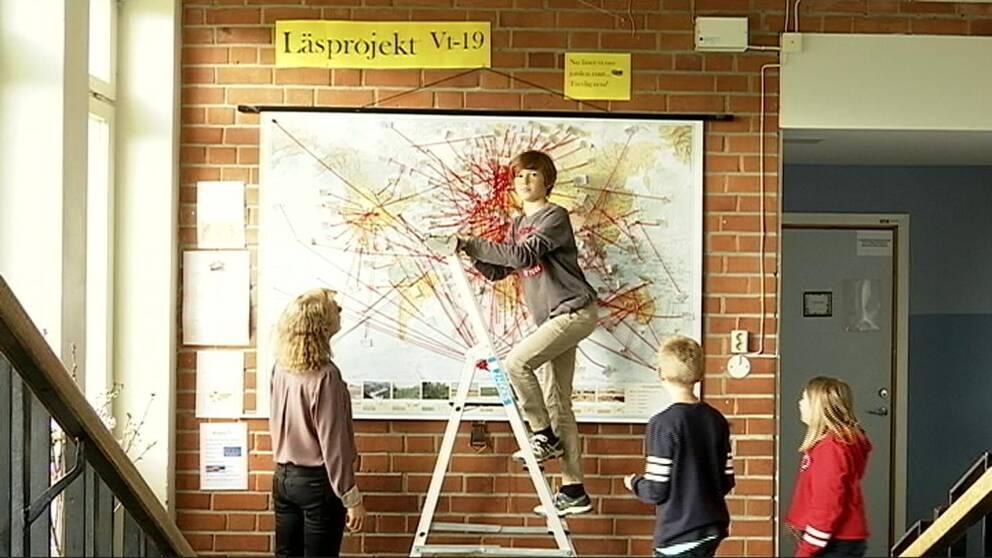 Karta med röda streck. Elever på Stallarholmsskolan i Strängnäs. Pojke klättrar upp för stege. Lärare tittar på elev och karta.