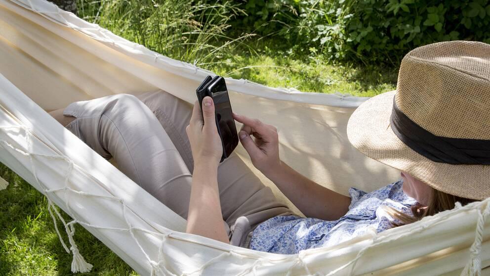 En person med hatt ligger i en hängmatta och surfar på mobilen.