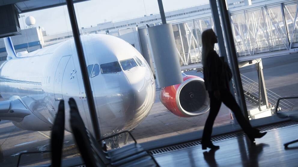 Flygplan och kvinna som går på en flygplats.