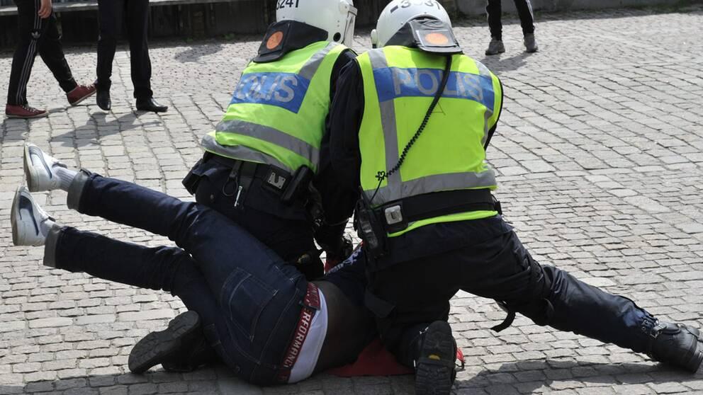 Två polis håller ner en demonstrant.