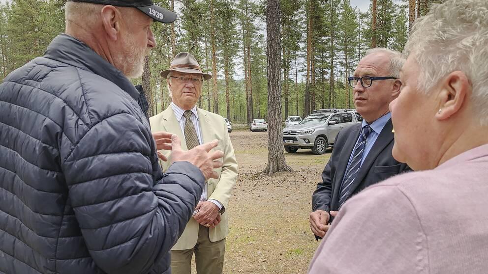 Kung Carl Gustaf samtalar med Per Bill och två boende i brandområdet i Kårböle.