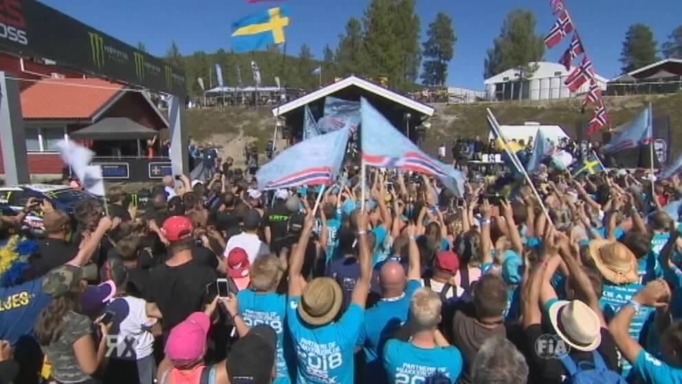 Folk firar med flaggor på rallycorss-tävling