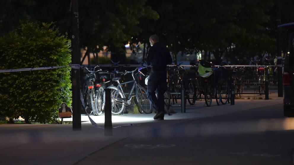 En polis lyser med ficklampa på marken.