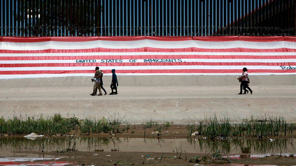 Människor går vid gränsen mellan USA och Mexiko.