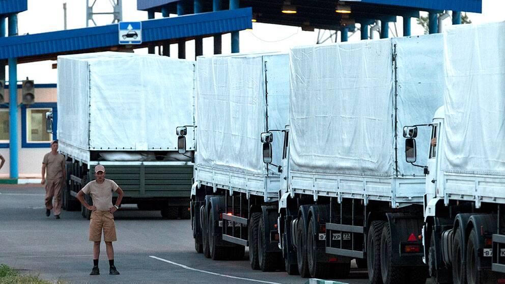 En förare står bredvid konvojen med ryska hjälpsändningar som har parkerat nära gränsstationen vid Donetsk, mellan Ukraina och Ryssland.