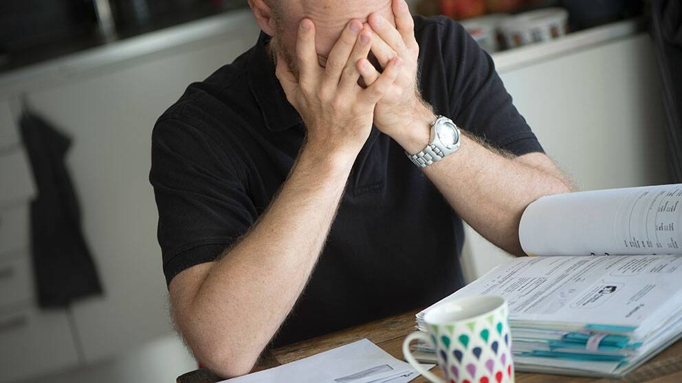 En bekymrad man sitter vid köksbordet med sina obetalda räkningar.