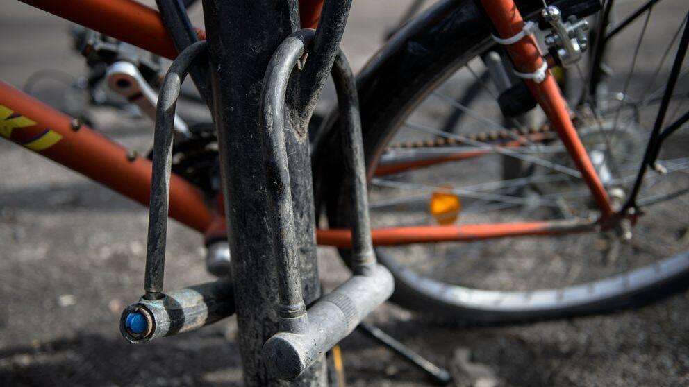 En cykel står parkerad i ett smutsigt cykelställ. Två cykellås hänger från cykelstället.