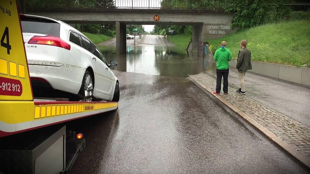 Översvämmning under viadukt. bil som bärgas