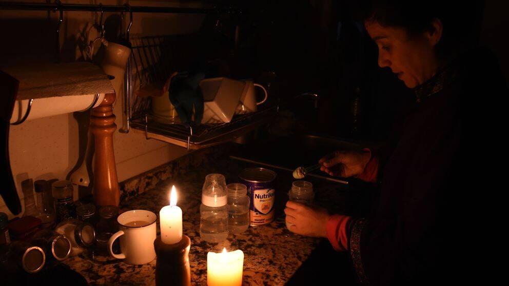 Kvinna blandar mjölkersättning i sitt kök.