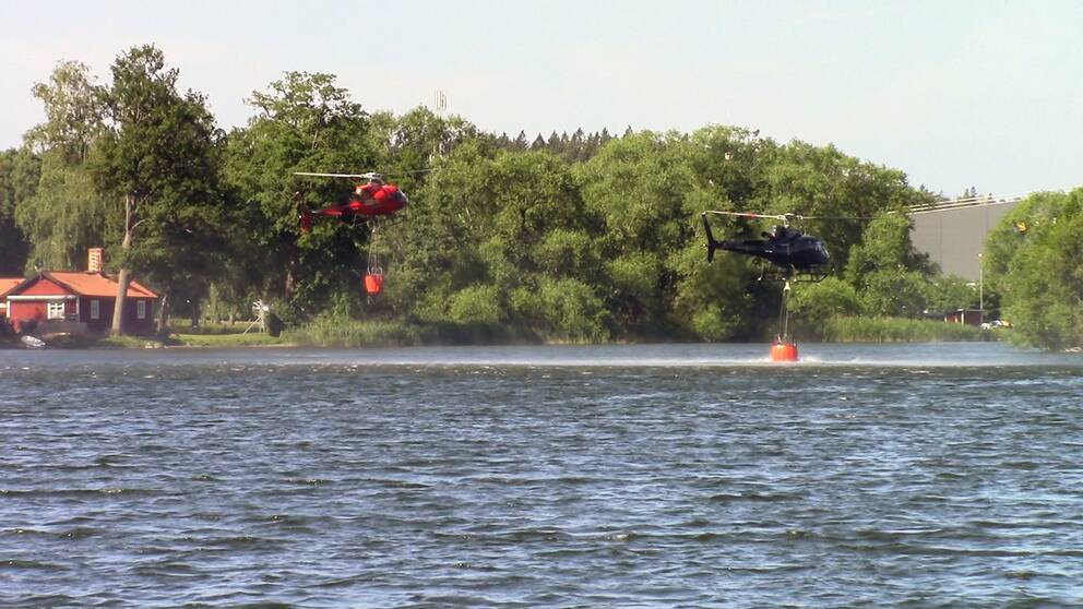 Helikoptrar hämtar vatten från Norrviken för att vattenbomba brand på Järvafältet.