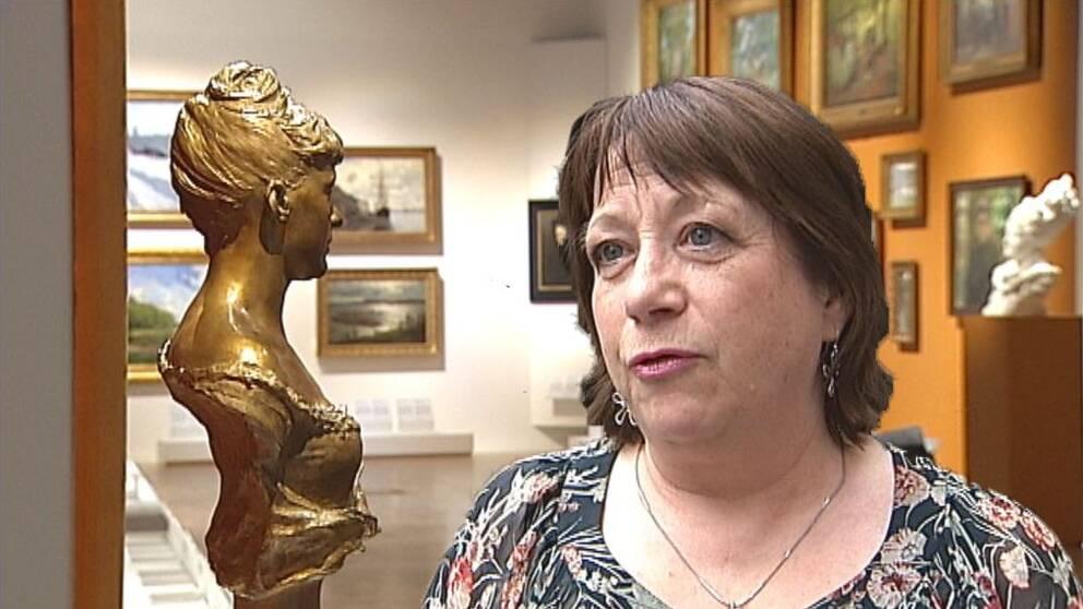 en medelålders kvinna som intervjuas inne på museum