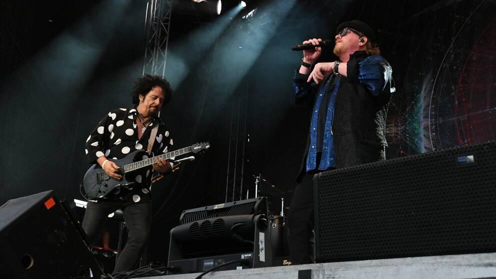 de två bandmedlemmarna – medelålders män – på scen, en spelar gitarr, en sjunger