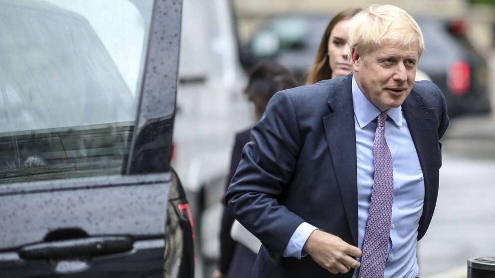 Boris Johnson kliver ut en bil.
