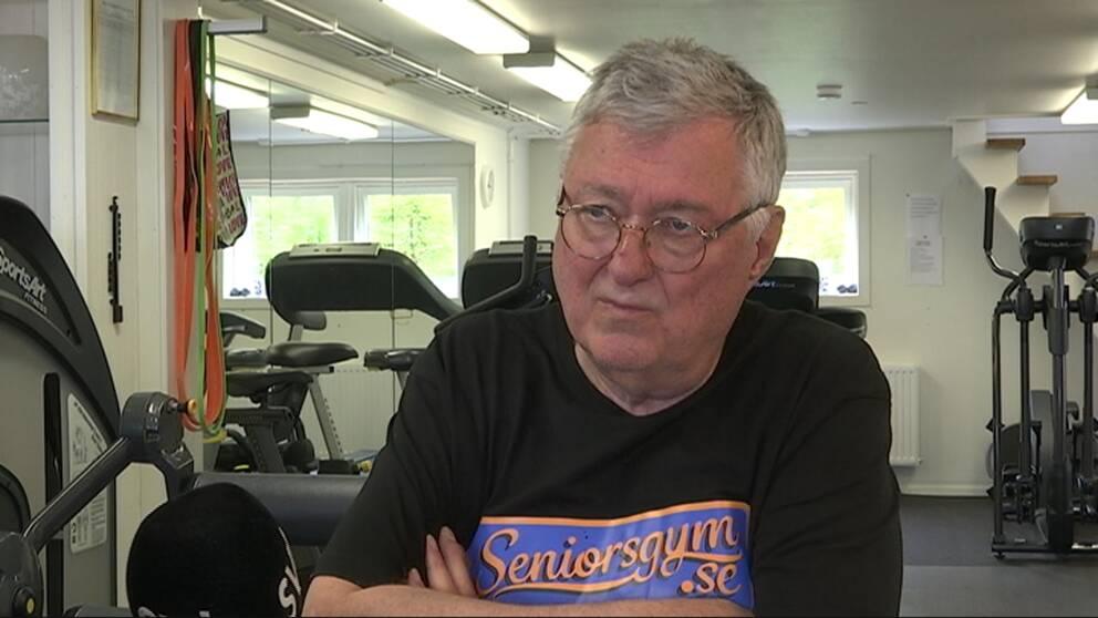 Man i svart t-shirt som sitter i ett gym.