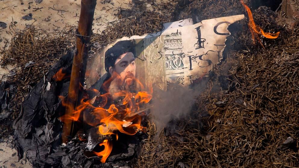 Bild på IS-ledaren Abu Bakr al-Baghdadi i lågor.