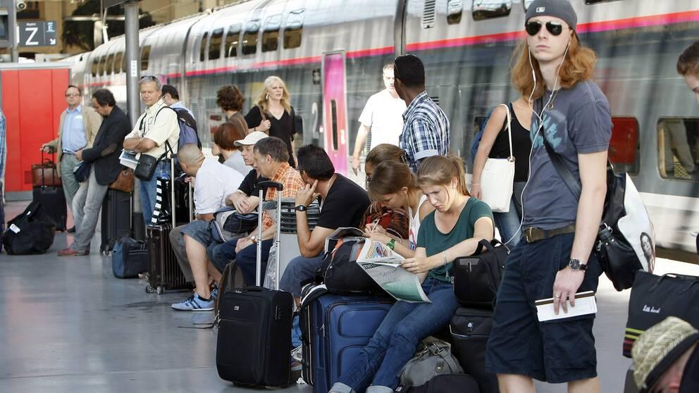 Människor som väntar på en tågperrong.