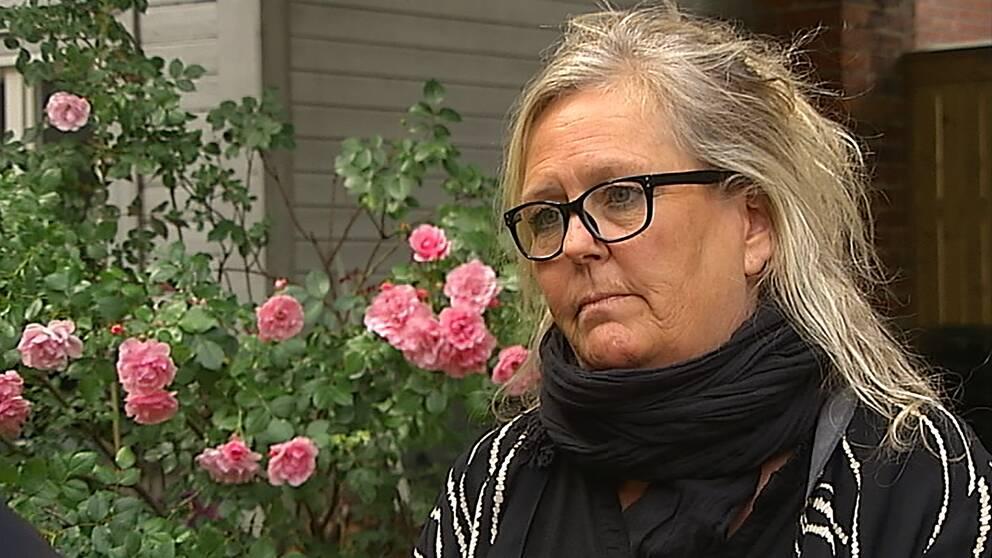 Volontären Viktoria Sterner står framför en rosenbuske