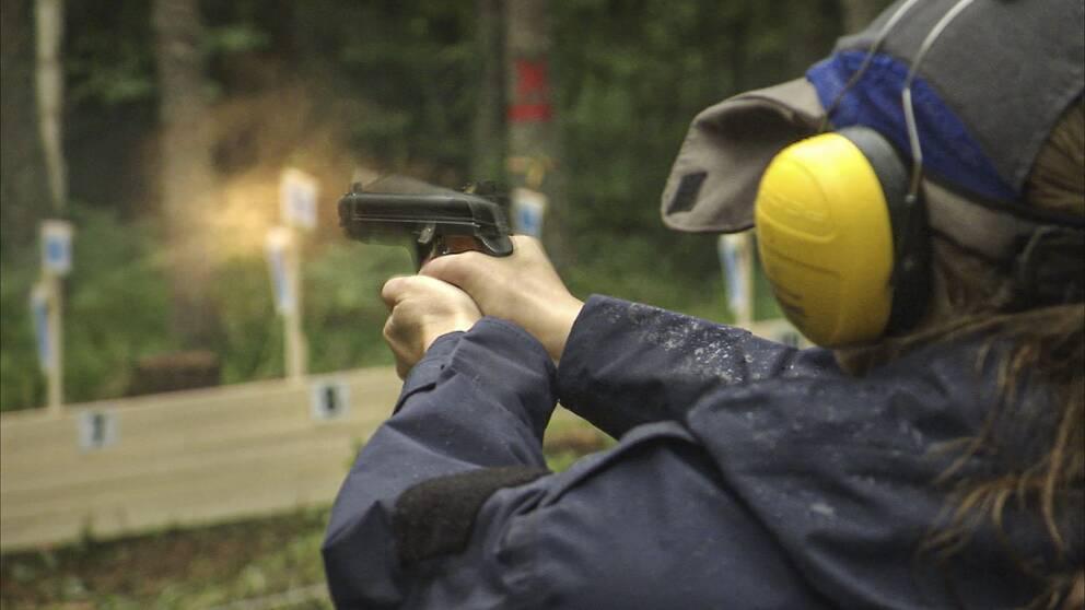 Skytt avlossar skott mot måltavla.