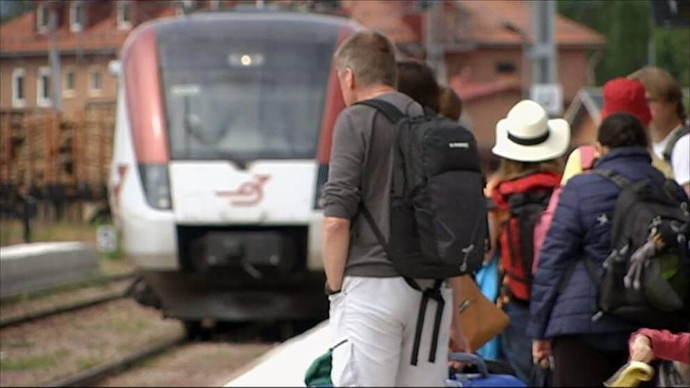Tåg i Bergslagen tåg. Människor på perrong.