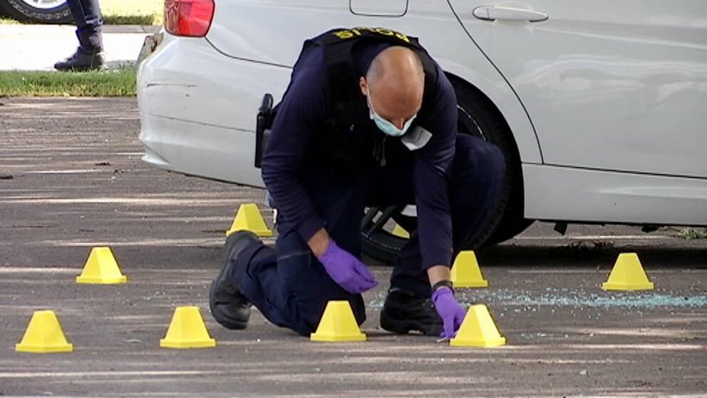 En polis med munskydd och handskar jobbar med markeringar på marken på en asfaltyta, en bil bakom