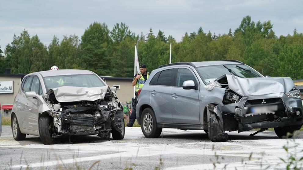 Två bilar som frontalkrockat samt en polisman i bakgrunden som pratar på sin walkie talkie.