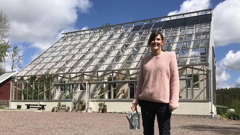 Susanne Andersson framför sitt hus i Havredal. På taket syns solpanelerna och solcellerna.