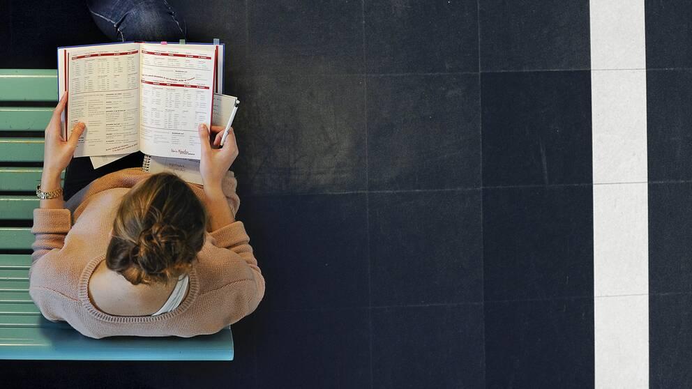 En kvinna sitter på en turkos bänk med en lärobok. Bilden är tagen uppifrån.
