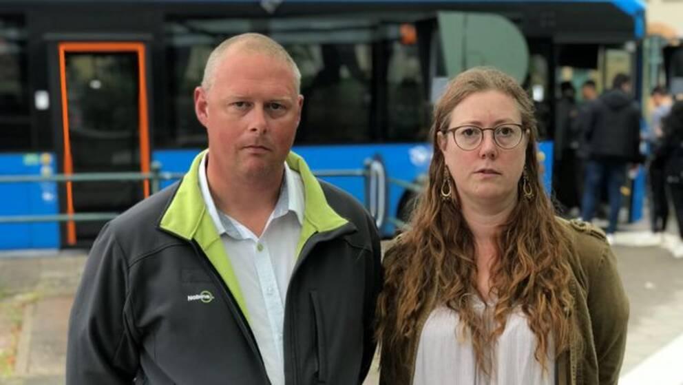 Busschaufförerna Mikael RylanderJenny Gustavsson framför en västtrafikbuss.