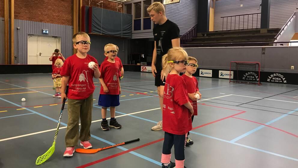 Barn med skyddsglasögon och innebandyklubbor i en gympasal.