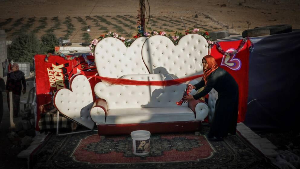 En kvinna torkar av soffan som brudparet ska sitta på.