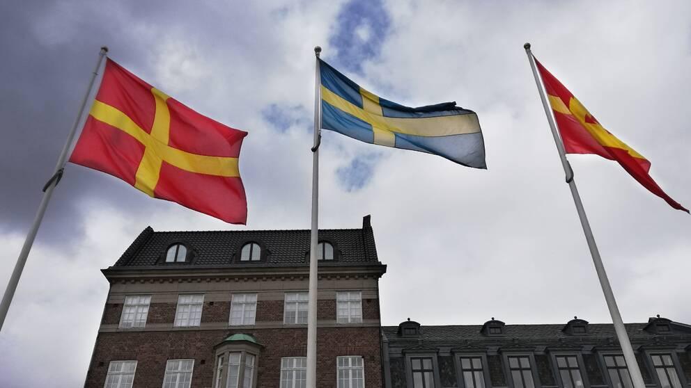 Två skånska rödgula flaggor vajar på varsin sida om den svenska flaggan på Stortorget i Lund, då det under dagen firades Skåneländska flaggans dag.