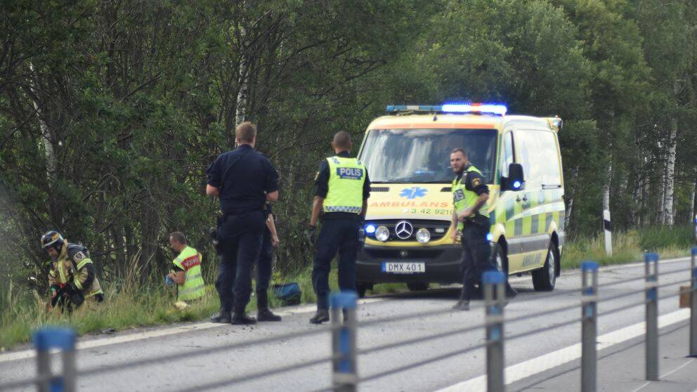 En ambulans med blåljus står på vägen som har ett vägräcke i mitten. Man ser poliser och personer från Räddningstjänsten som står på vägen och går i diket.