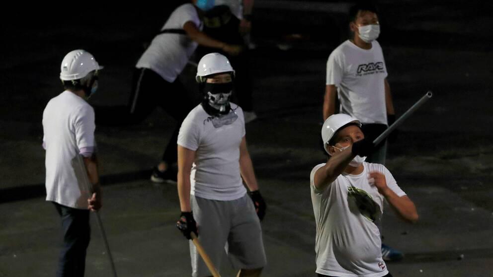 Fem män i vita t-shirtar med käppar i händerna.