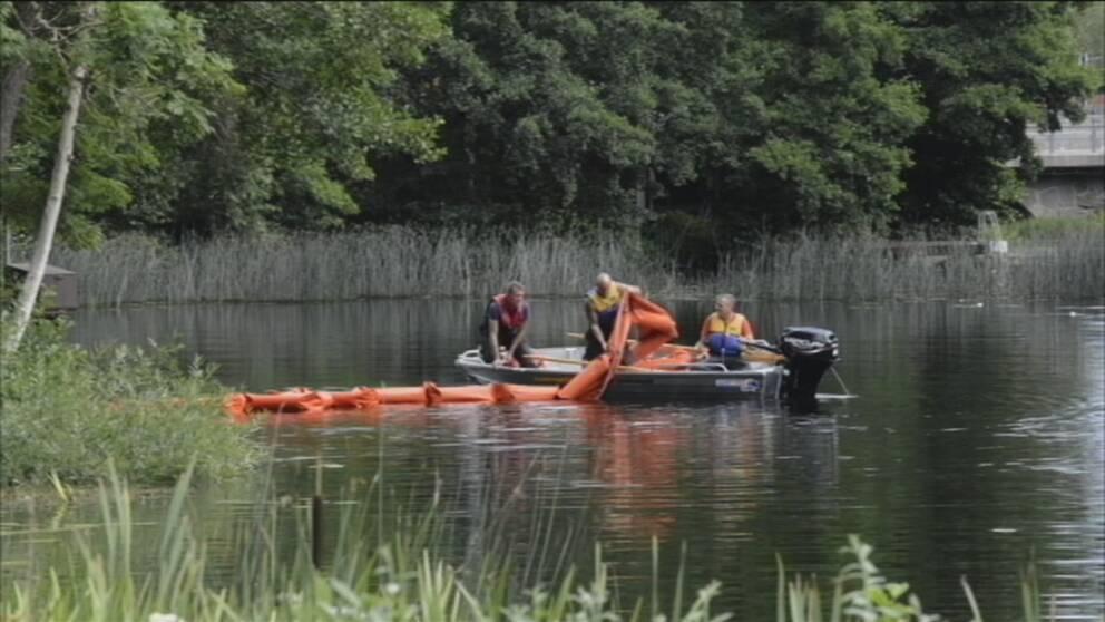 Räddningstjänsten har en liten båt med orange länsar som de lägger ut som en barriär i vattnet för att stoppa utsläppet i ån.