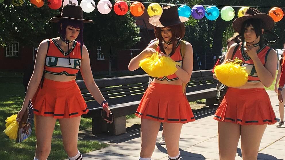 Tre tjejer i cheerleadin-dräkter och cowboyhattar