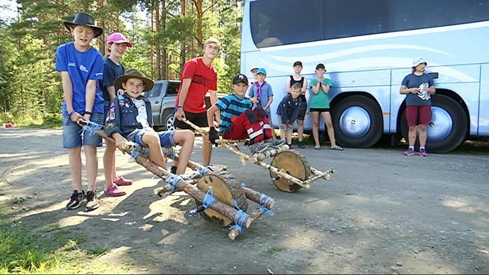 Flera scouter står uppställda framför kameran tillsammans med skottkärror som de själva har byggt. I bakgrunden syns en buss och flera träd.