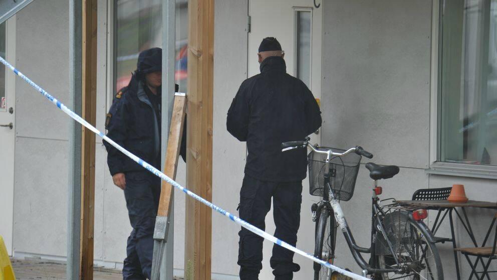 Poliser utanför lägenhet med avspärrningar.