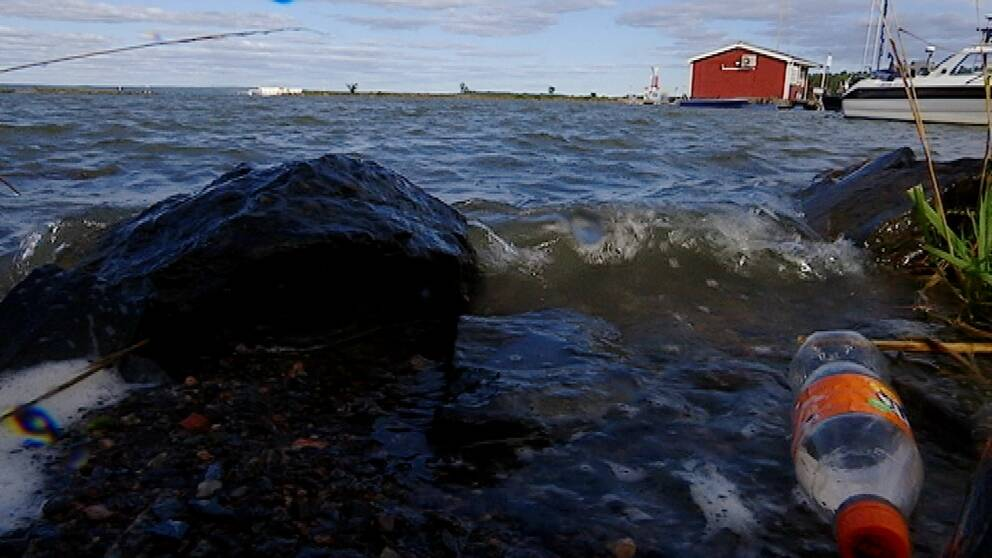 Vågor slår in mot stranden, i förgrunden syns en pet-flaska.