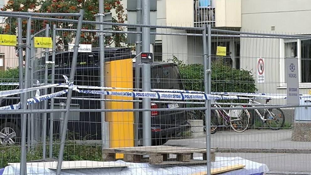 Polisband sitter på ett staket vid ett hyreshus. I bakgrunden står en svart skåpbil.