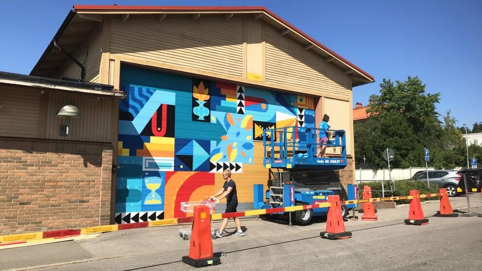 Artist målar en garageport.