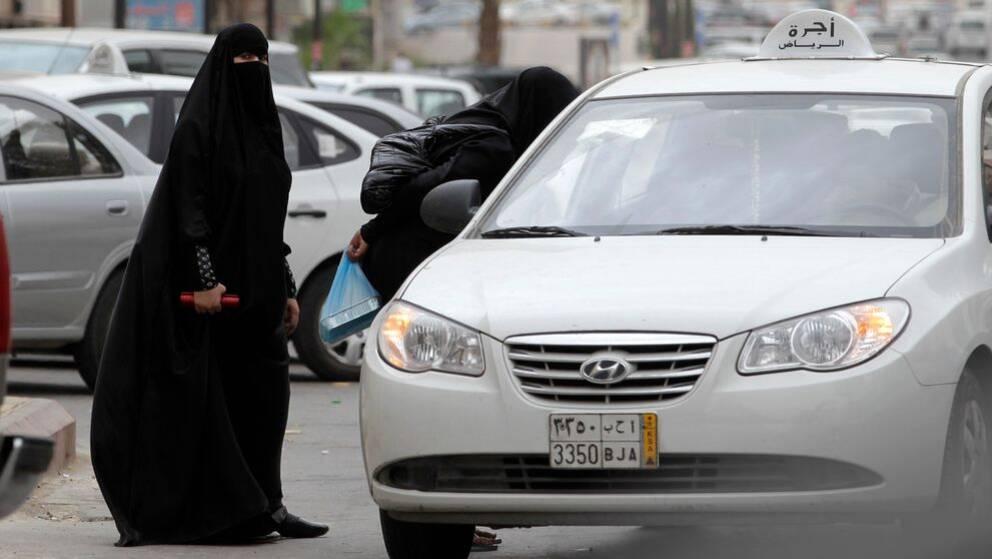 Två saudiska kvinnor står vid en bil.