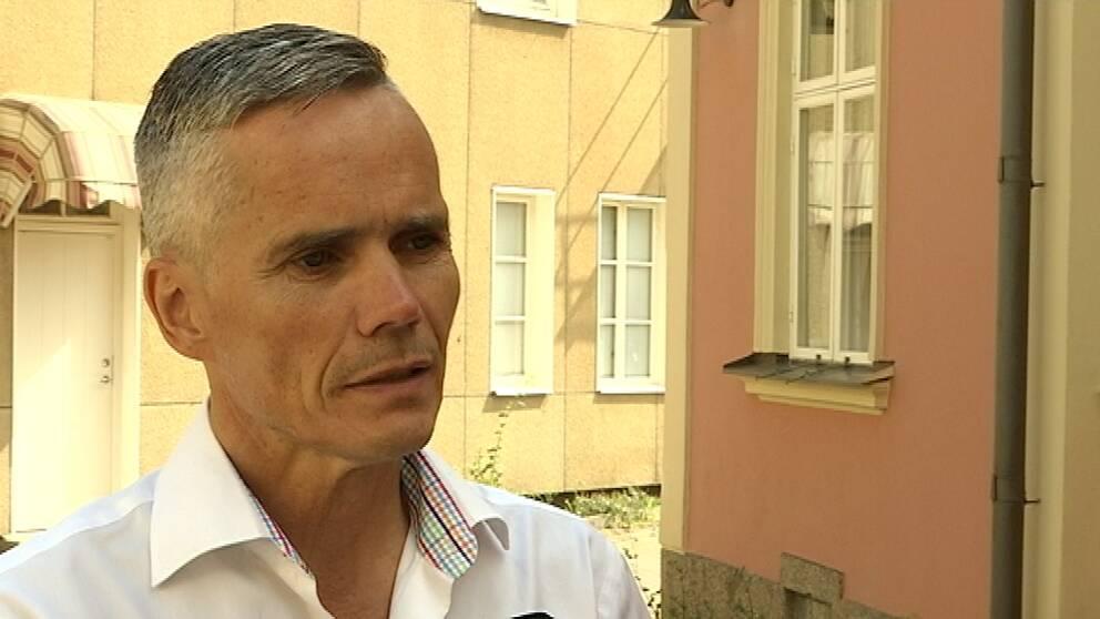 Porträttbild på Michael Malmgren som står vid Hotel du Nord som har sålts som lägenheter.