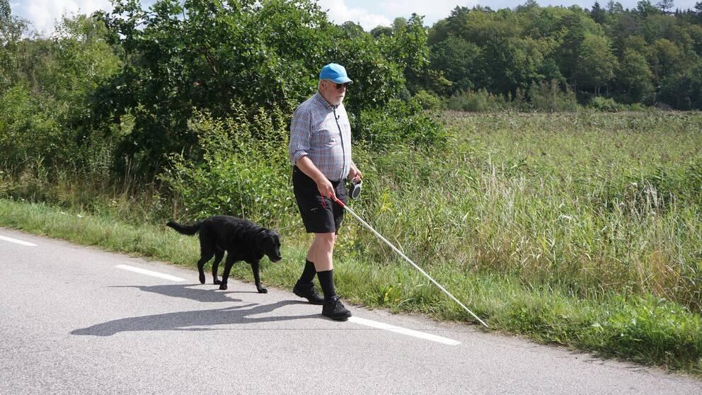 Stellan Jacobsson går längs med en väg med sin ledarhund.