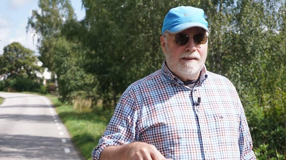 Stellan Jacobsson, i skjorta och blå keps, framför en landsväg.