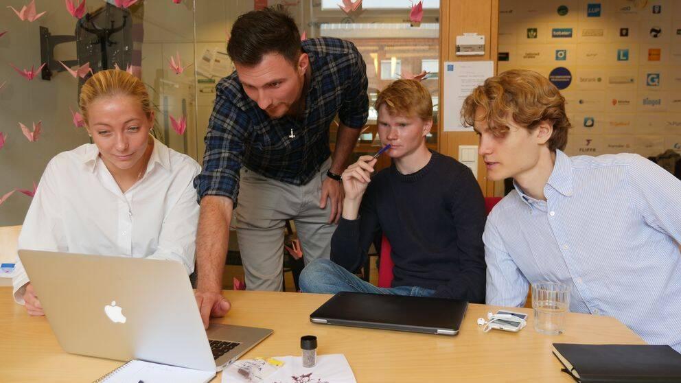 Ruth Öberg, Angelo Demeter, Fredrik Åkerman och Leo Wezelius från KTH-startupen Volta Greentech tittar på en laptop.
