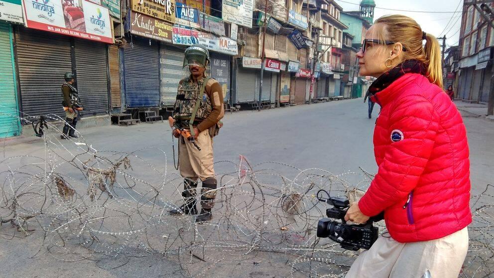 Kvinna i röd jacka står på gata och filmar med videokamera. I bakgrunden syns två soldater med vapen och avspärrning.