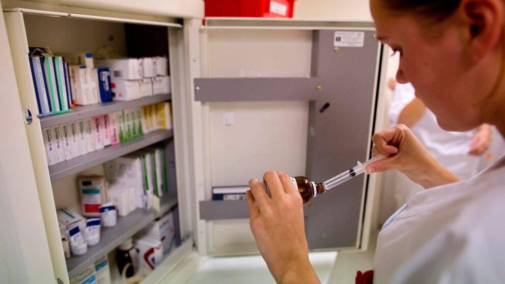 Närbild på tjej i profil med vit vårdrock som förbereder en spruta med medicin. Hon står framför ett medicinskåp.