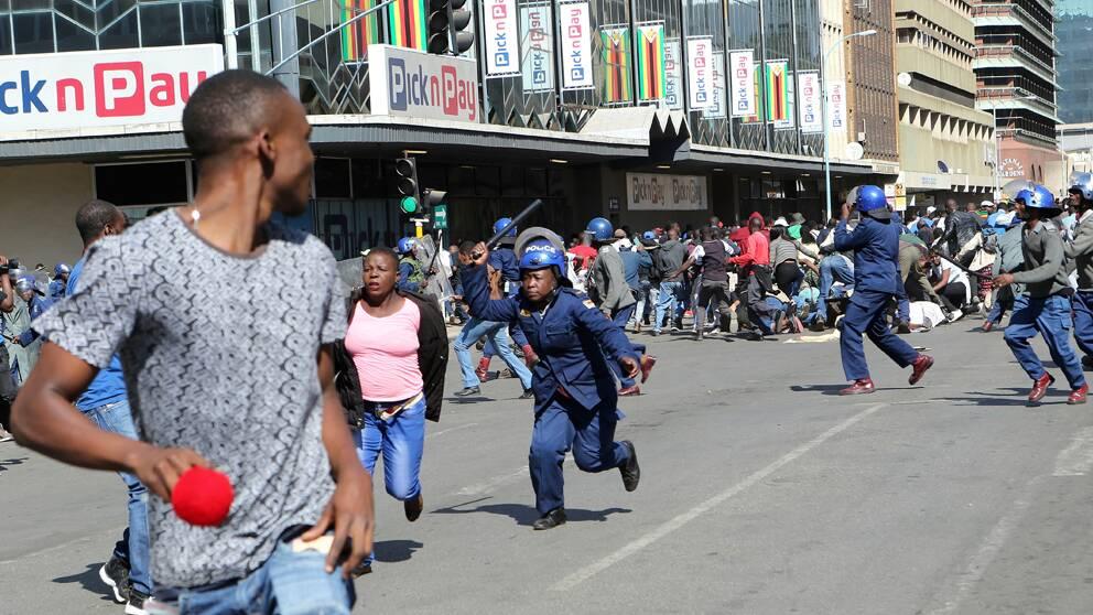 Polisen som jagar demonstranter i Zimbabwes huvudstad Harare under fredagen.