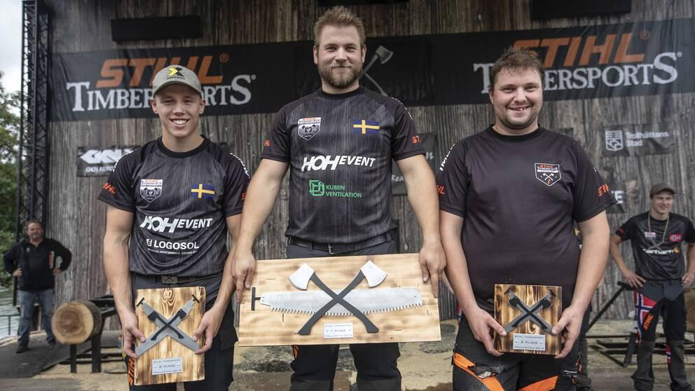 tre män står på prispall, håller plaketter av trä och metall