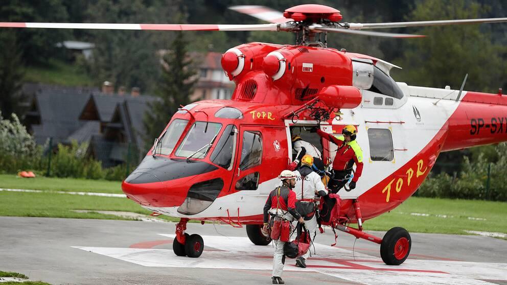 Räddningsarbetare går ombord på en helikopter för att delta i insatsen.
